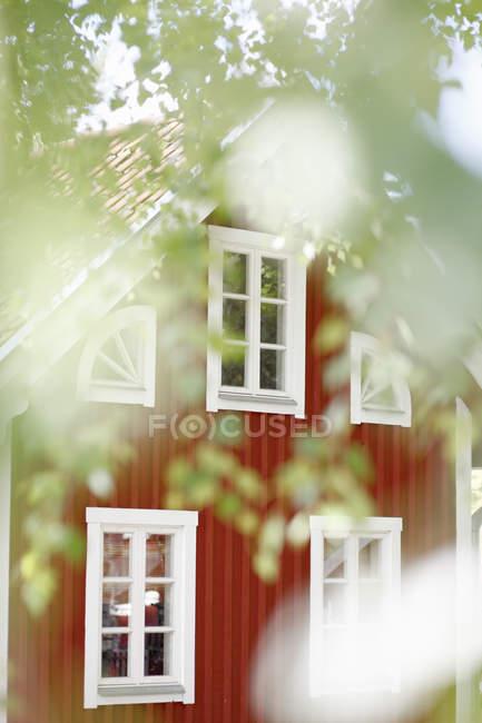 Falu casa de madeira vermelha em vegetação exuberante — Fotografia de Stock