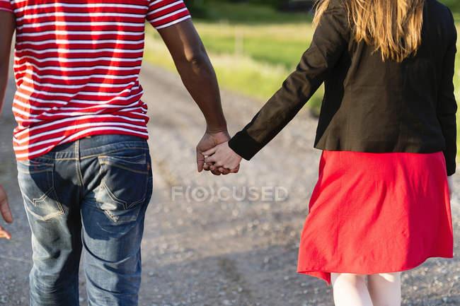 Вид сзади на среднюю взрослую пару, держащуюся за руки — стоковое фото