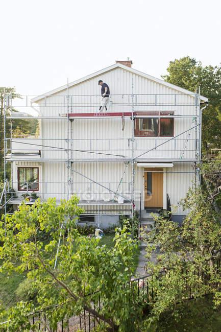 Man on scaffolding fixing siding on house, selective focus — rear