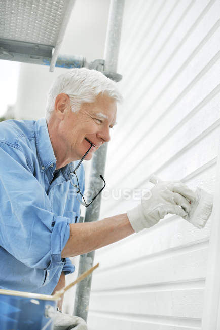 Smiling senior man painting wall — Stock Photo