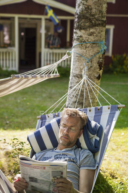 Man reading in hammock, focus on foreground — Stock Photo