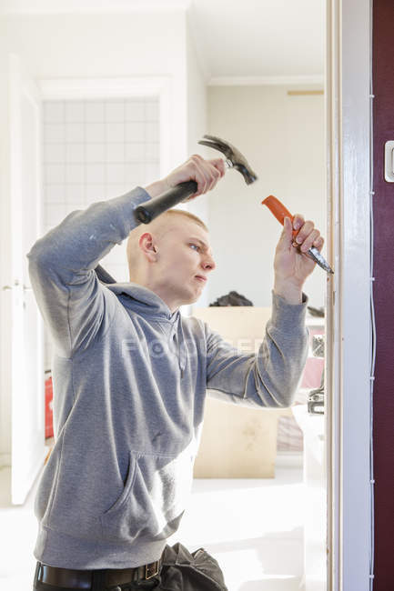 Young man renovating house, focus on foreground — Stock Photo