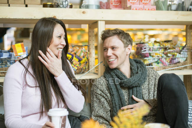 Man and woman laughing in shop, differential focus — Stock Photo