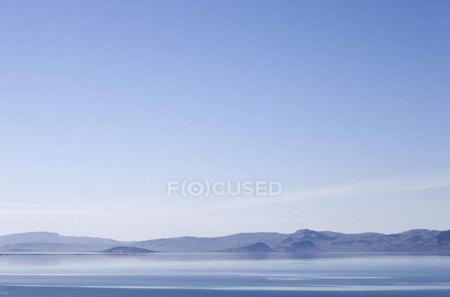 Mountains and still lake water under blue sky — Stock Photo