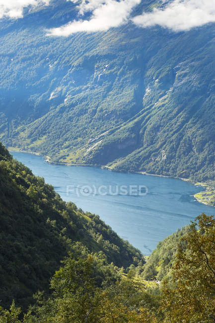 Elevated view of lake and green covered mountains — Stock Photo