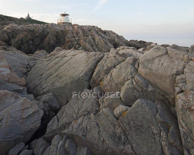 Craquage des rochers côtiers avec petit phare sur le dessus — Photo de stock
