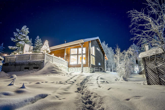 Cottage on snowcapped hill illuminated at night — Stock Photo