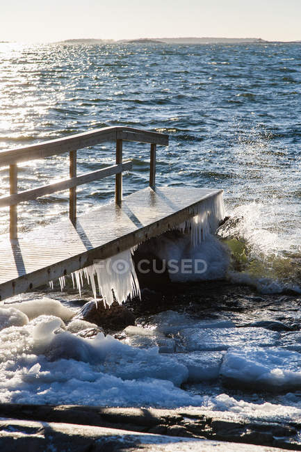 Front view of pier with icicles in sunlight — Stock Photo