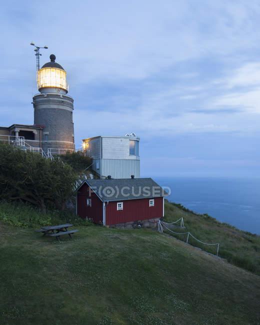 Illuminated lighthouse on green hill at dusk — Stock Photo