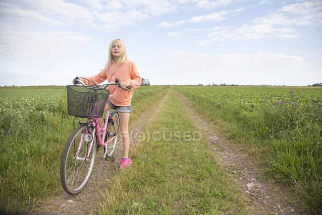 Menina loira de pé com bicicleta na estrada de terra no campo verde — Fotografia de Stock