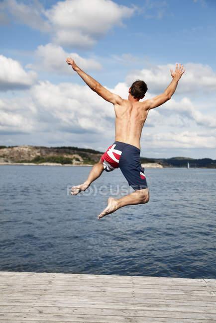Rückansicht des Menschen ins Wasser springen — Stockfoto