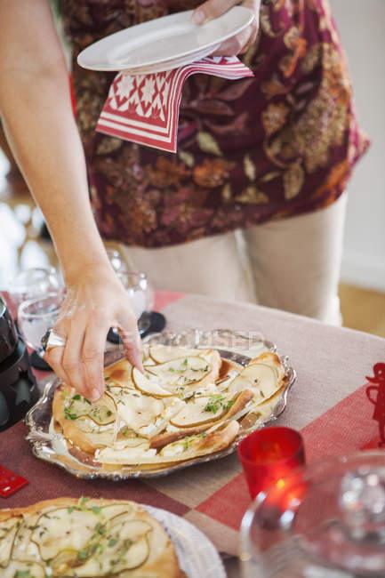 Main femme prenant des grignotines de plaque sur la table — Photo de stock