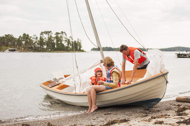 Family with child wearing life jackets on sailboat — Stock Photo