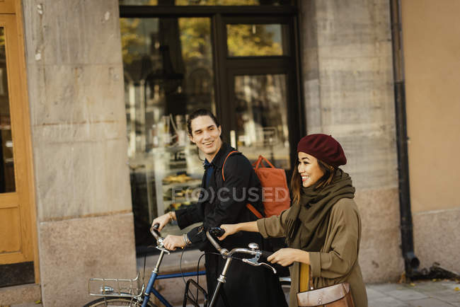 Two people walking with bicycles, selective focus — Stock Photo
