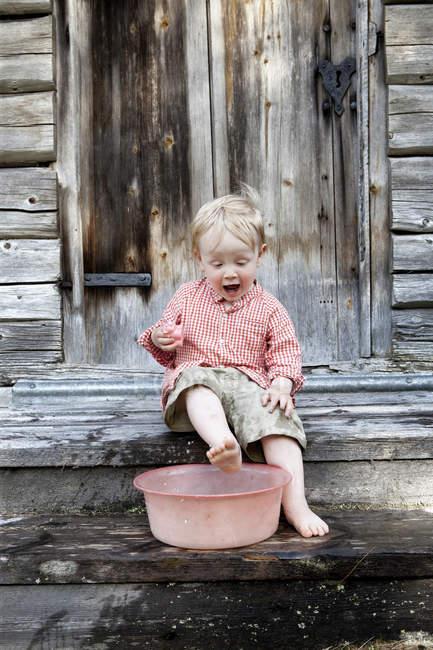 Boy washing feet on wooden steps — Stock Photo