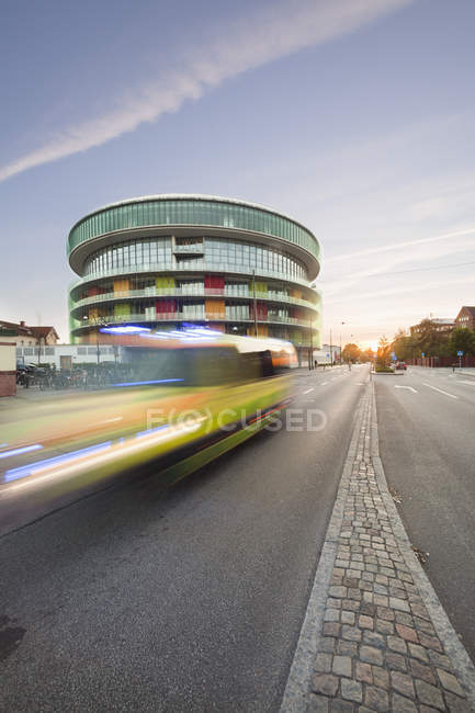 Blurred ambulance moving on street with building on background — Stock Photo