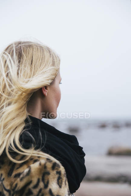 Giovane donna bionda guardando il mare — Foto stock