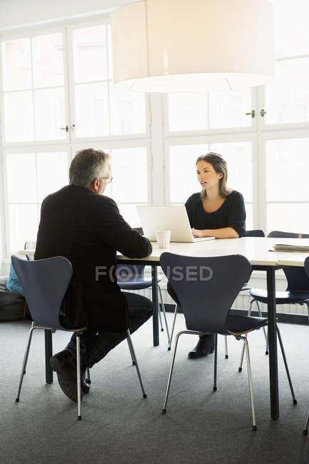 Giovane donna e uomo maturo seduto alla scrivania in ufficio — Foto stock