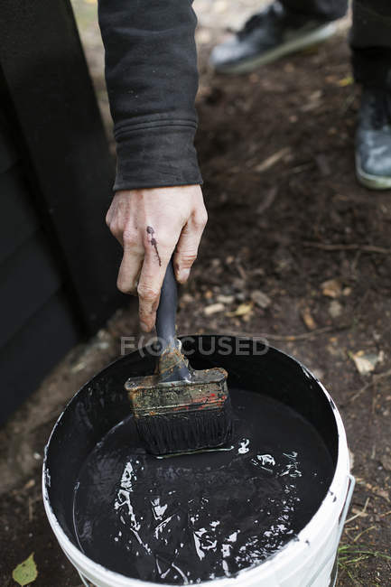 Man dipping brush in can with black paint — Stock Photo