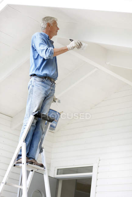 Senior man standing on ladder and painting wall — Stock Photo