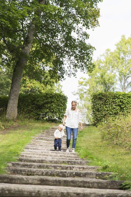 Femme qui marche avec les fils dans le parc — Photo de stock