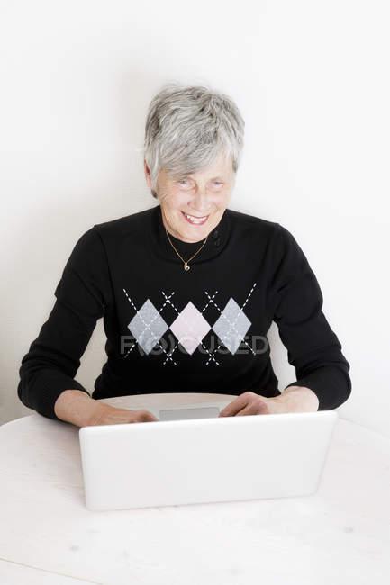 Mulher sênior usando laptop e sorrindo — Fotografia de Stock