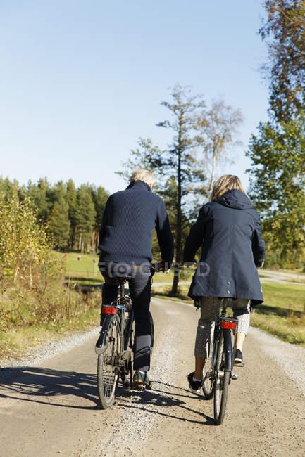Vue arrière de l'homme et la femme vélo — Photo de stock
