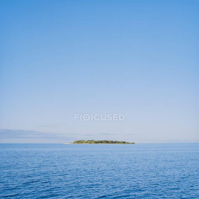 Vista lejana de la isla verde en el mar bajo el cielo azul - foto de stock