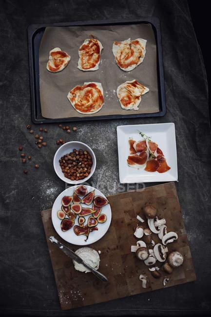 Vue de dessus des ingrédients de la Pizza sur la table et sur le plateau — Photo de stock