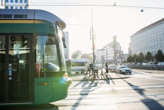 Cyclists and tram on street, lens flare — Stock Photo