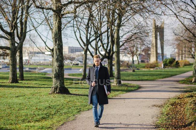 Homme d'affaires marchant le long de l'allée du parc, mettant l'accent sur le premier plan — Photo de stock