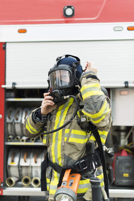 Weibliche Feuerwehrmann Schutzmaske aufsetzen — Stockfoto