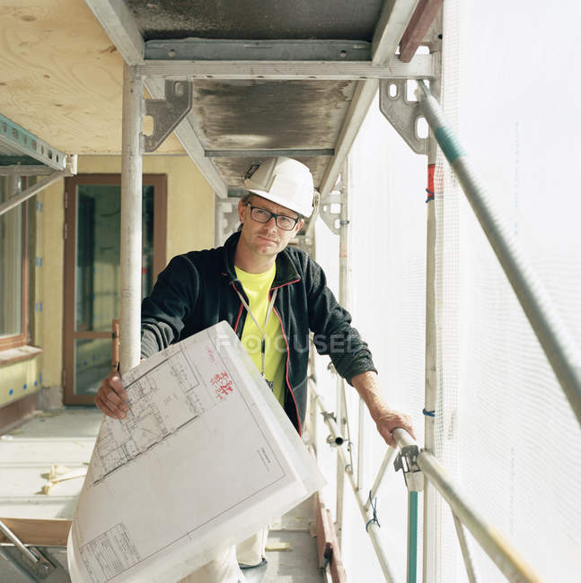 Portrait of construction worker with blueprints looking away — Stock Photo