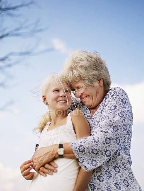 Portrait of grandmother embracing granddaughter, focus on foreground — Stock Photo