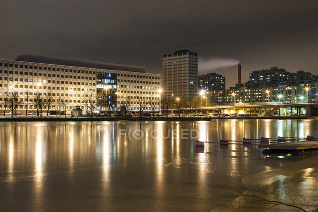 Buildings illuminated at night reflecting in water — Stock Photo