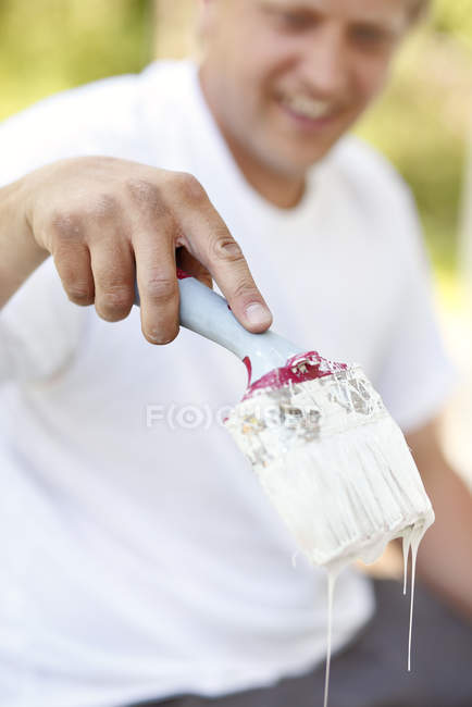 Man holding paintbrush with dripping paint, focus on hand — Stock Photo