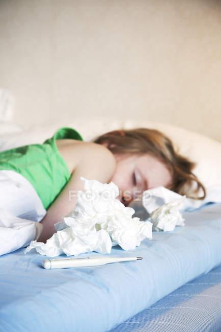 Chica acostada en la cama con termómetro, enfoque selectivo - foto de stock