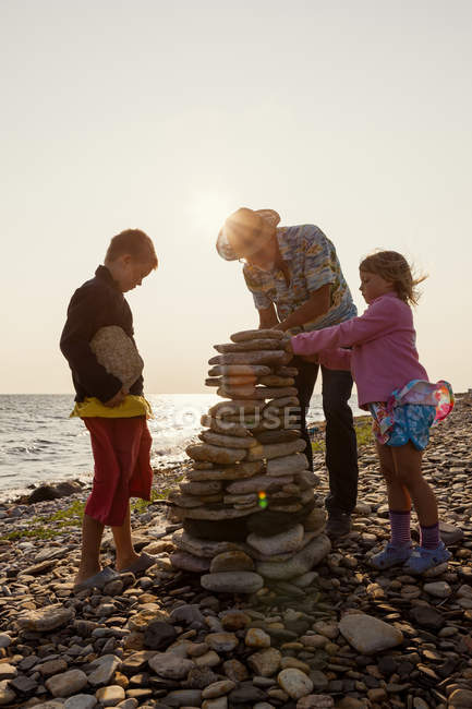 Grandfather and grandchildren, making stone heaps — Stock Photo