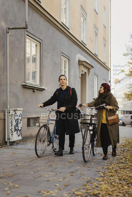 Двоє людей, які ходять з велосипедами, зосереджені на передньому плані — стокове фото