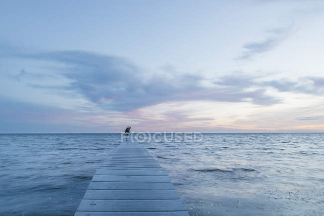 Женщина, стоящая на пирсе у моря — стоковое фото