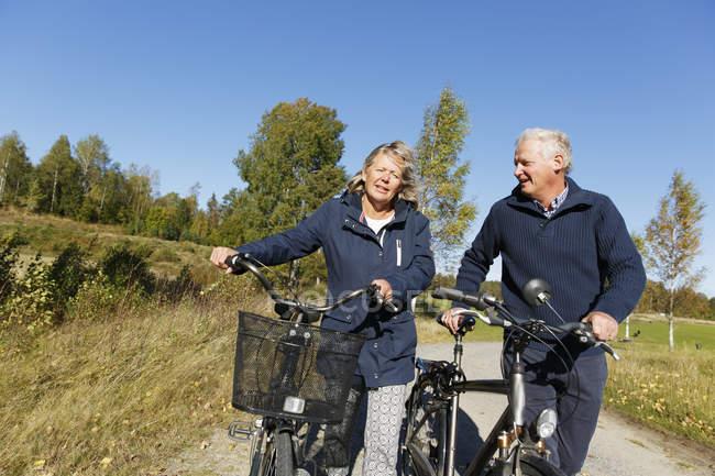 Senior homme et femme mature qui marche avec des vélos — Photo de stock