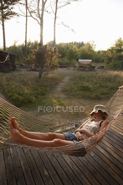 Woman taking nap in hammock with panama hat on face — Stock Photo