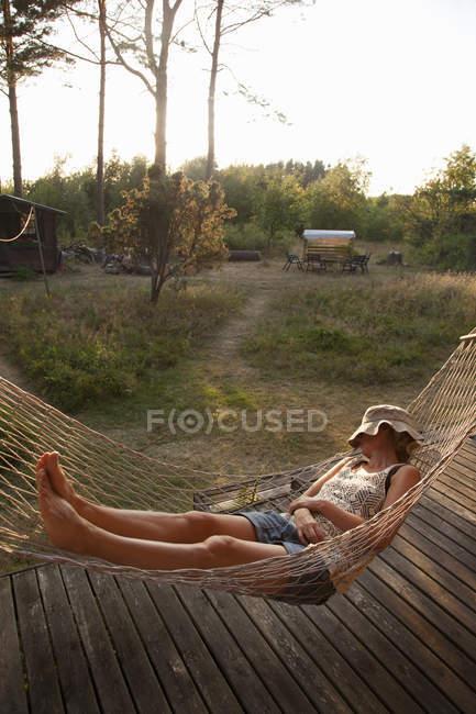 Donna che fa un pisolino in amaca con cappello panama sul viso — Foto stock