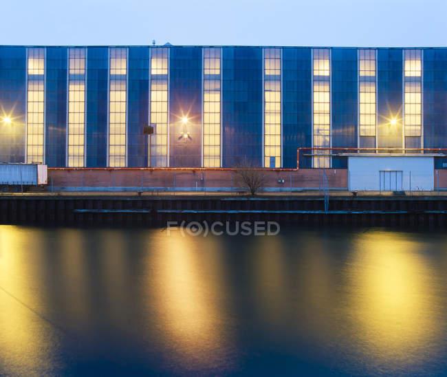 Illuminated windows of building above harbor — Stock Photo