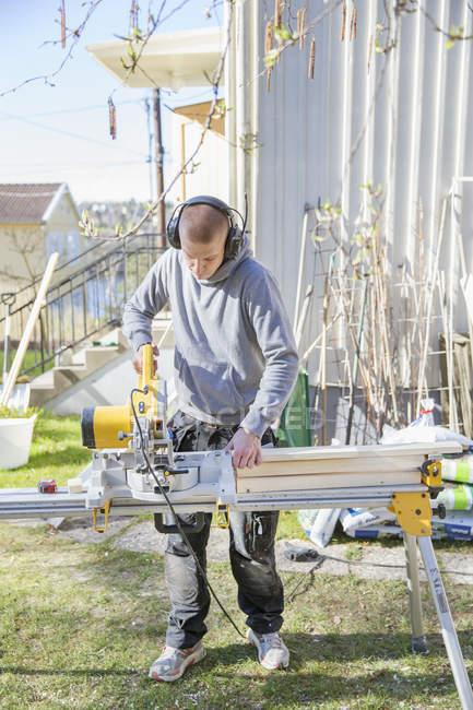 Homem trabalhando no quintal, foco em primeiro plano — Fotografia de Stock