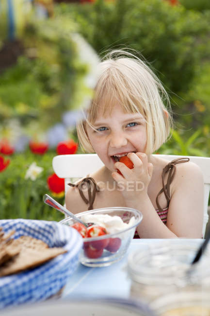 Girl eating strawberries with cream, selective focus — Stock Photo