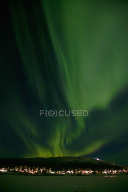 Vista de la ciudad nocturna y aurora boreal cielo iluminado - foto de stock