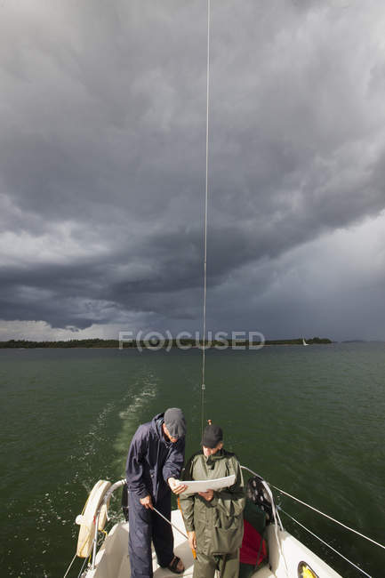 Two men looking at map on boat, selective focus — Stock Photo