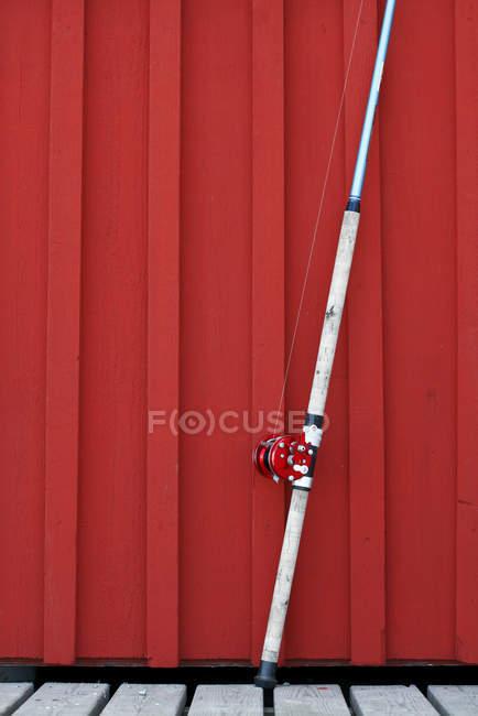 Рыболовный прут перед красной стеной — стоковое фото