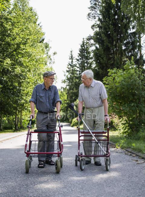 Two senior men with walking frames talking — Stock Photo